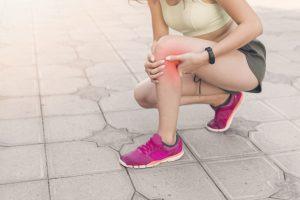 atleta-femenina-agachado-pavimento-tener-dolor-rodilla_23-2147888989